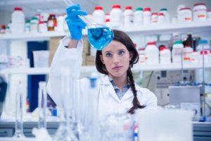 female-scientist-examining-liquid-in-flask